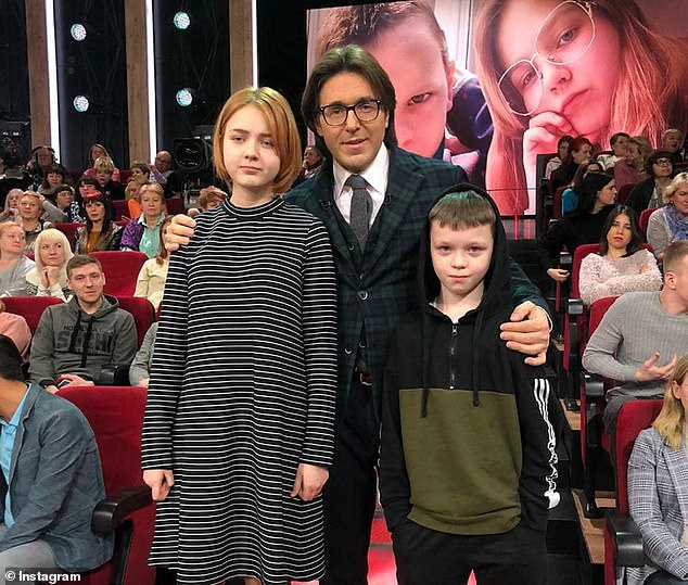 Russian TV host Andrey Malakhovv posing with Darya and Ivan. He interviews the children about Darya