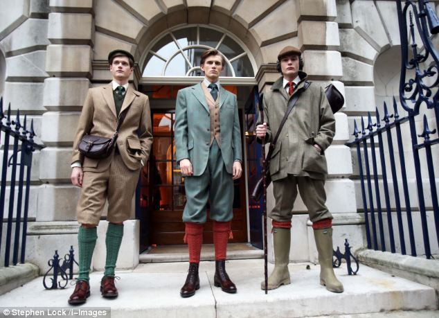 The models wear flat caps, tweed suits with waistcoats and one holds a walking stick resembling the style adopted by the 1920s characters in the period drama