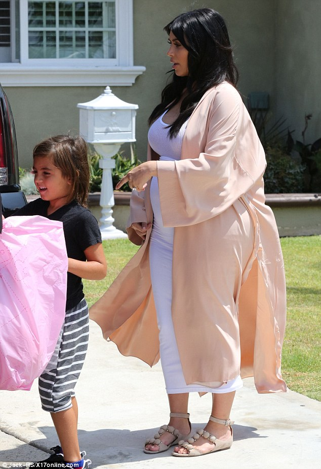 Her little helper: Mason carried a pink bag while Kim gave direction from behind him