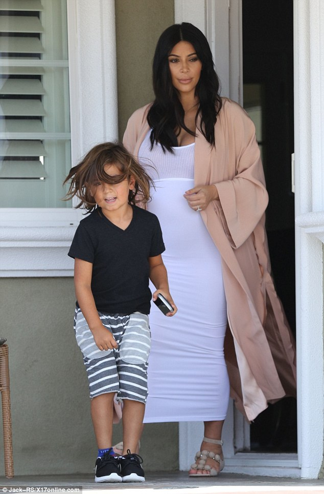 Cute look: The E! star was also showing off her large pregnancy bump in a white tank top, white tube skirt pulled up high and a long, silky light pink coat